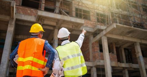 Two men wearing reflective vests and hard hats and holding plans looking at a building that is under construction.