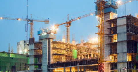 Three cranes can be seen amid a brightly lit multistorey construction site.