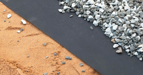 A geotextile on top of sand and covered by gravel.