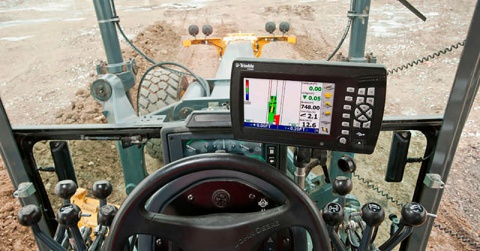 A view from inside the cabin of a motor grader onto the grader control system.