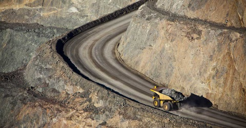 A fully loaded mining haul truck driving up a gravel haul road.
