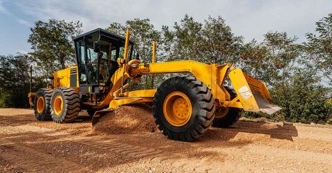 A motor grader moving and levelling earth .