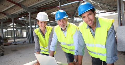A female and two male engineers at a construction site.