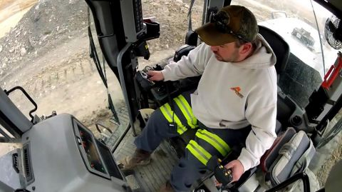 An inside view of the cabin of a motor grader in which a male operator is sitting.