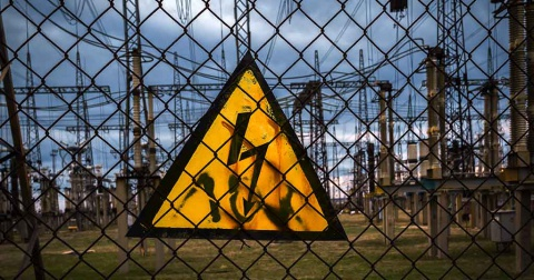 A yellow high voltage warning sign on a fence with a power plant in the background.