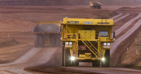 Three mining haul trucks driving along a wide gravel haul road.