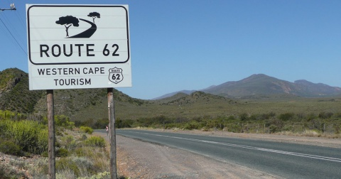 A route62 road sign next to a tar road with Karoo landscape in the background.