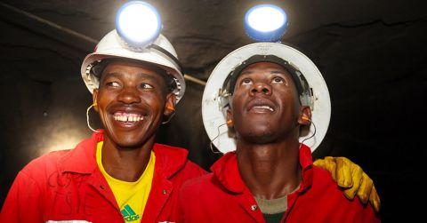 Two African miners wearing helmets and headlamps standing in a mine tunnel.