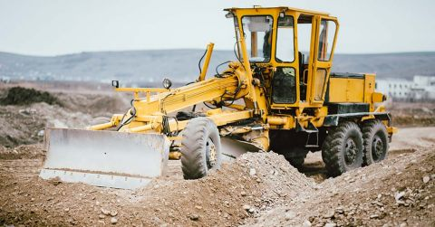 A motor grader amid a pile of earth,