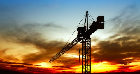 The upper part of a crane amid a firy and cloudy orange sunset.