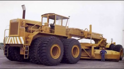 A man standing in front of, and being dwarfed by a massive ACCO motor grader.
